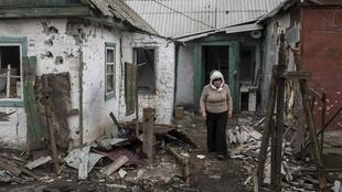 A woman walks out of her damaged house in the town of Debaltseve, north-east of Donetsk, 17 March 2015